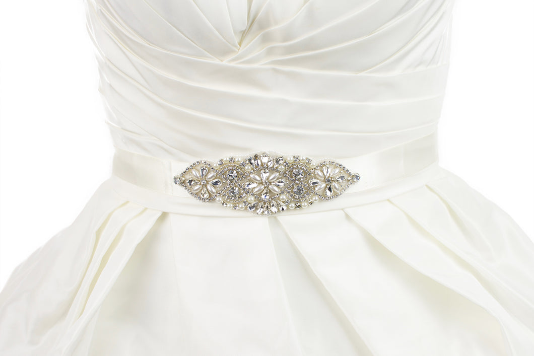 Small crystal and pearl bridal belt motif on an ivory ribbon worn on an ivory dress with white background