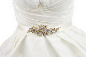 Pale Gold leaves and flowers motif on an ivory satin ribbon worn on an ivory bridal gown.