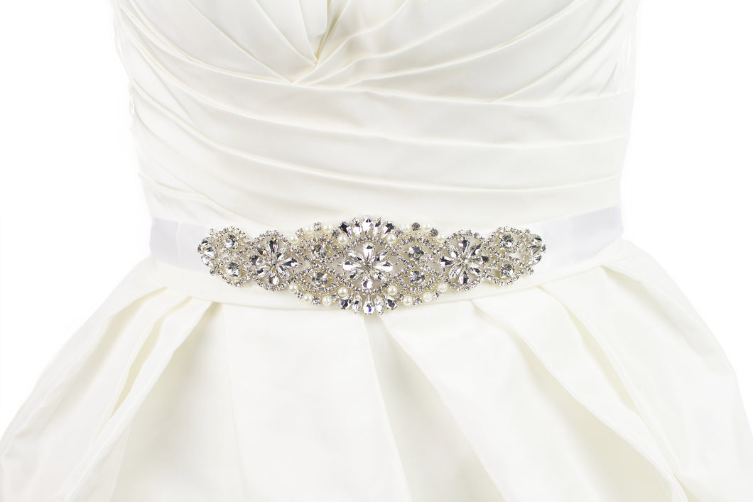 A bridal belt with crystals and pearls that is quite short on a satin ribbon worn on an ivory bridal gown