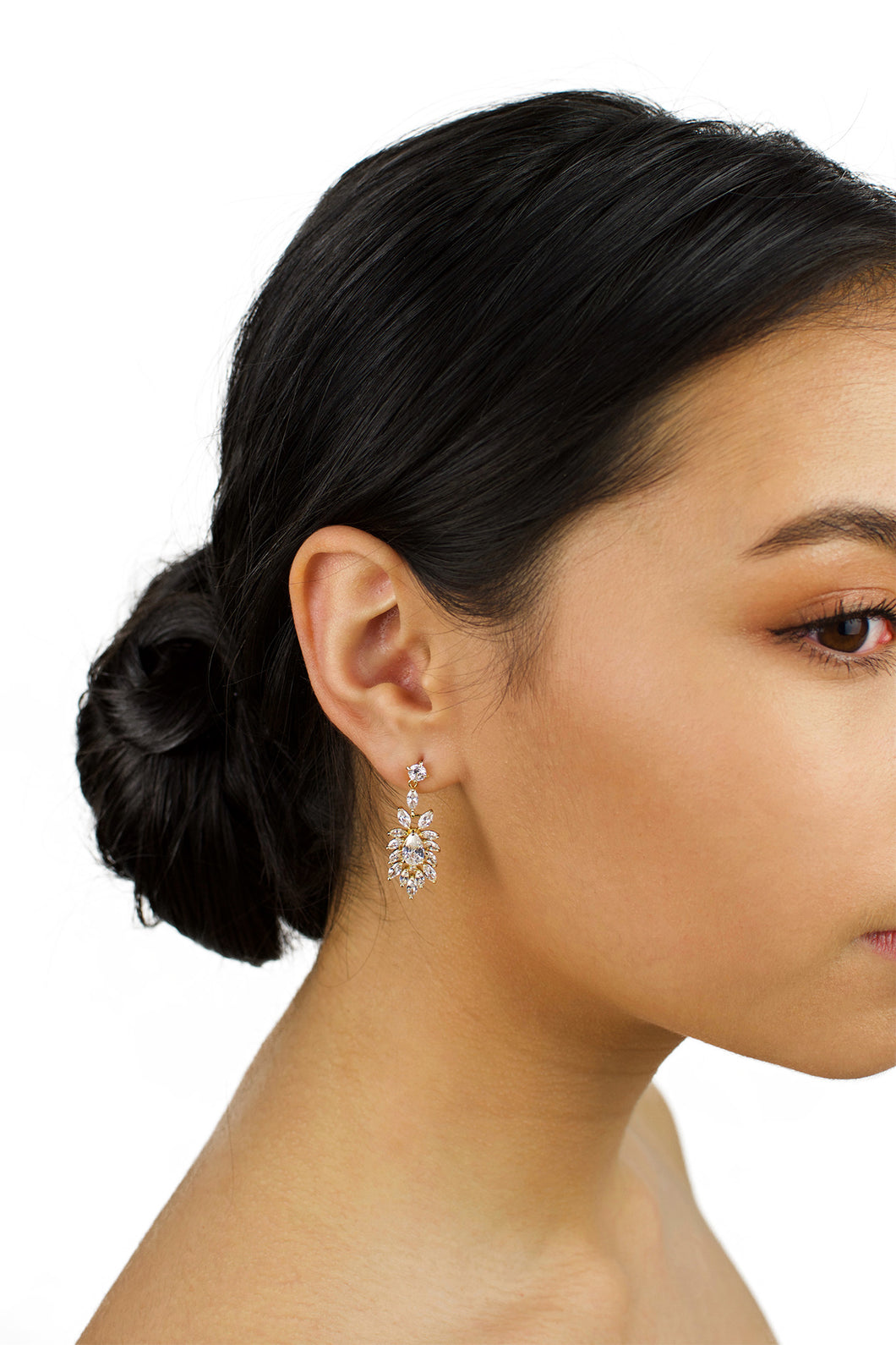 Model wears a gold drop earring in her ear with dark hair and a white background