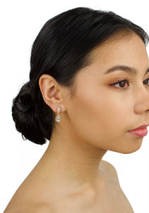 Very small gold drop earring worn by a dark hair bridal model with a white background