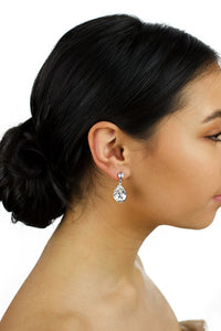 Dark haired model wears a silver earring with a clear Swarovski stone