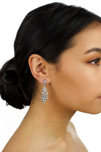 A model bride wears a crystal drop earring. She has dark hair and there is a white background