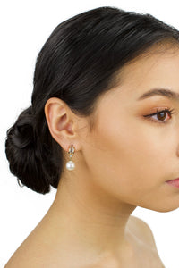 Small Gold and pearl drop earring worn by a dark haired bridal model