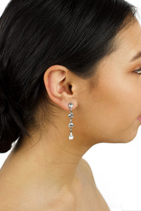 A dark hair model is wearing a long narrow earring in silver with clear stones