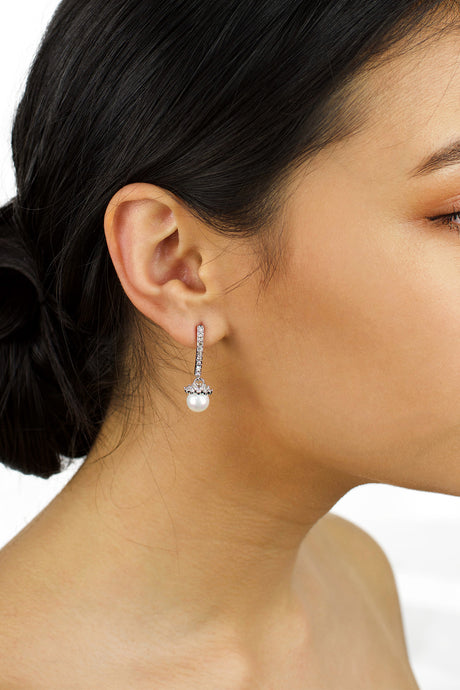 A dark hair model with a drop pearl earring in her ear