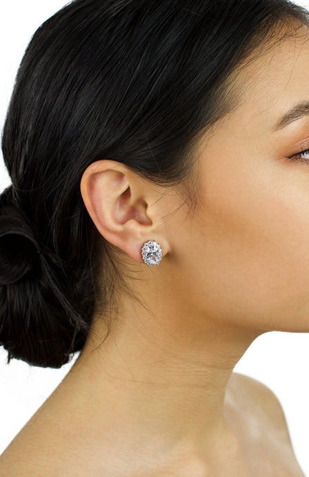 Dark haired bride wears a single stone stud earring  in one ear with a white background