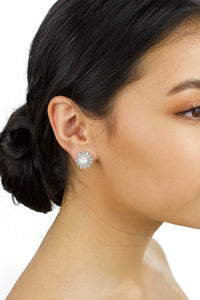 Model with dark hair up wears a stud earring of pearl and crystal with a white background