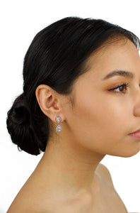 Small silver drop earring worn by a dark hair bride with a white background