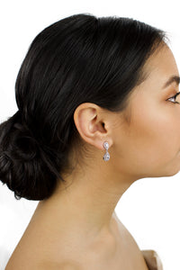 Small Silver pear shape earring worn by a bride with dark hair on a white background