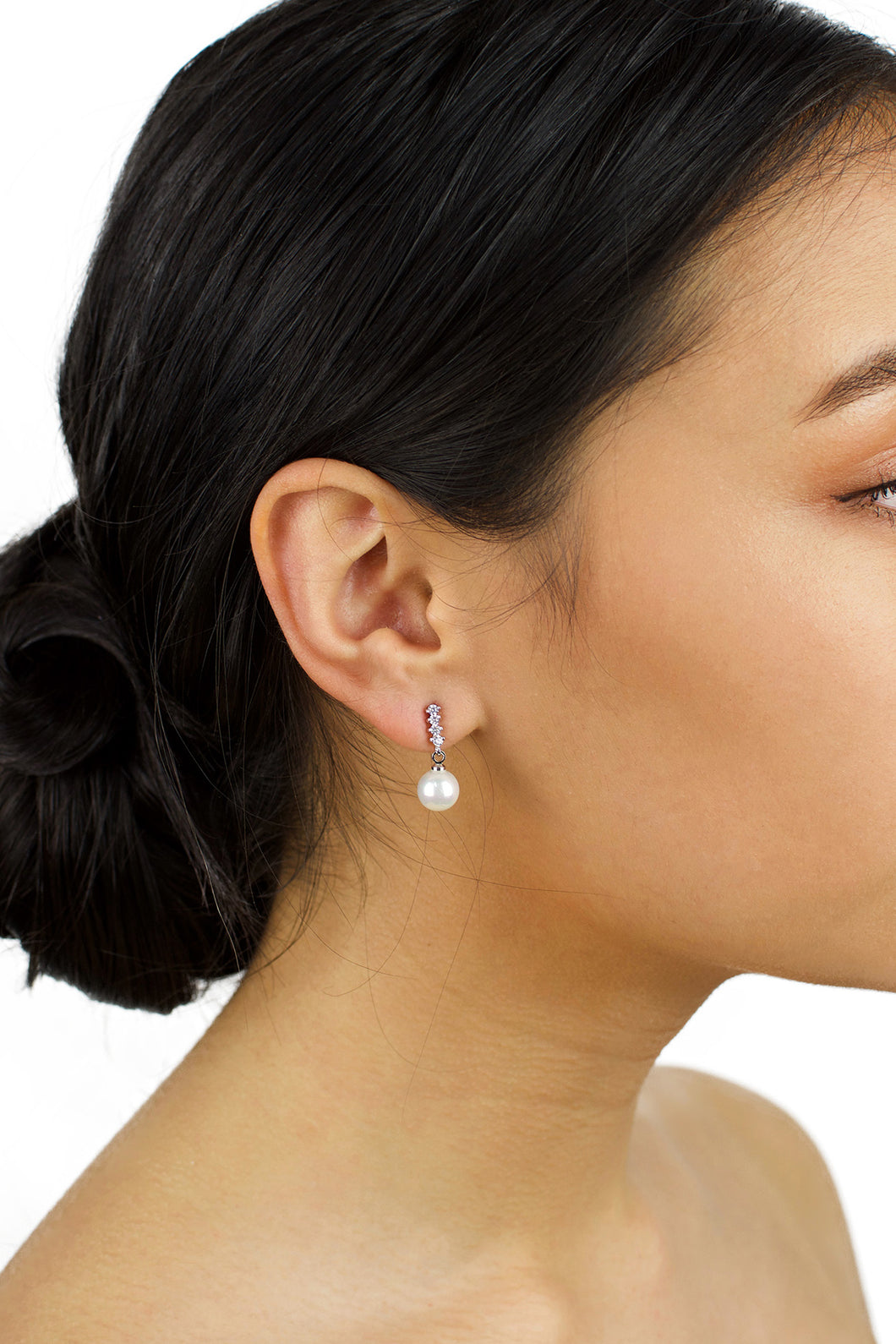 Dark Haired model wearing a single pearl drop earring with a white background