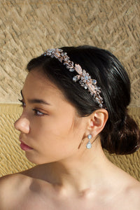 Dark haired model with long hair wears a side comb of pale rose parts leaves at the side of her head. With a stone wall background