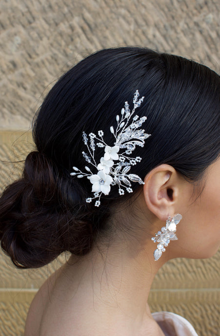 Dark Hair model wears a small silver flowers and seed pearls clip with a stone wall background