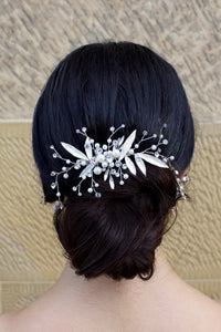 Silver leaf comb at the back of a brides head on dark hair with a stone wall backdrop