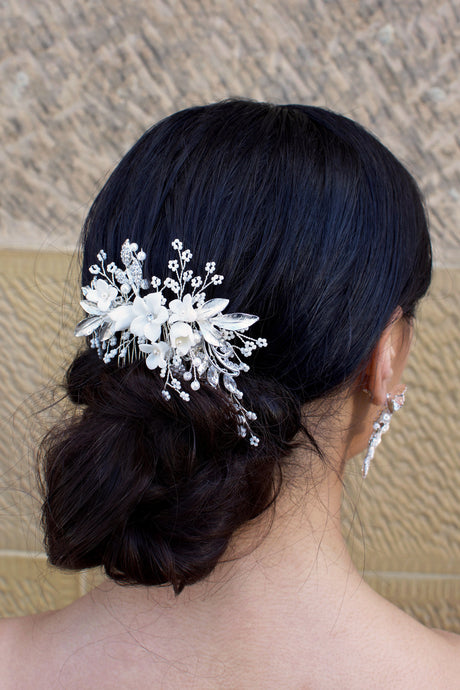 A dark haired Bride wears a silver and ceramic flowers comb at the side of her head.