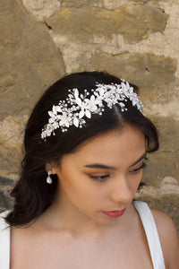 Black haired model wears a silver leaves headband with a wall backdrop