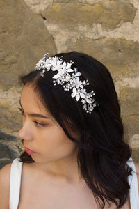 Dark hair bride wears a silver leaves bridal headband with a wall as backdrop