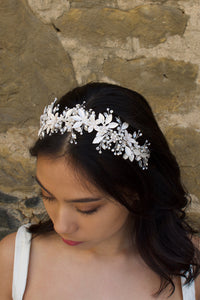 Model looks down wearing a silver leaves headband on her dark hair with an old wall behind