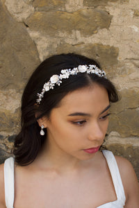Brown Haired model wearing a ceramic flower headband in silver with a stone wall background