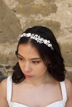 Load image into Gallery viewer, Black haired Bride wearing a White and Silver Flowers headband with a stone wall background