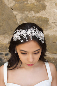 Silver and crystal headband worn by a bridal model at the front of her head