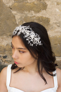Side view of a bridal model wearing a wide crystal headband for brides with a stone wall backdrop