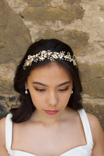 Load image into Gallery viewer, A front view of a model in front of a stone wall wearing a pale gold bridal headband on her forehead.