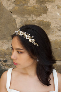 From a side view a Bridal Model with long black hair wears a gold headband of leaf shapes.