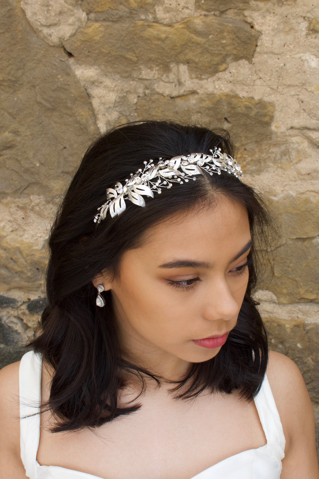 A silver bridal headband is worn by a black haired model with a stone wall in the background