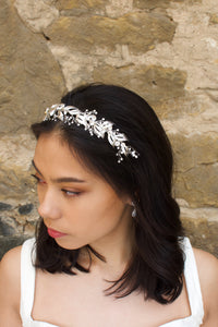 Looking to the left a model wears a beautiful silver bridal headband in her dark hair