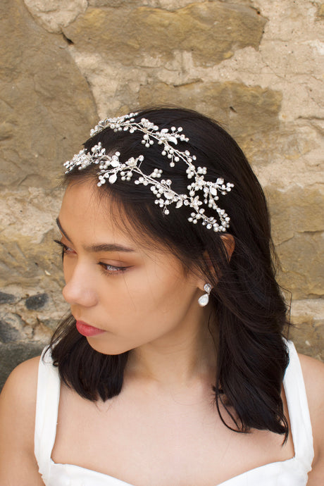 Silver double row headband on a black hair model with a pearl earring and a stone wall backdrop