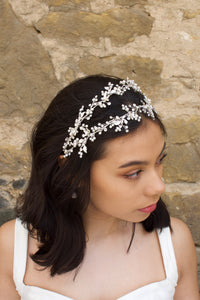 Black hair model looks to the side wearing a silver pearl handmade headband with a stone wall behind