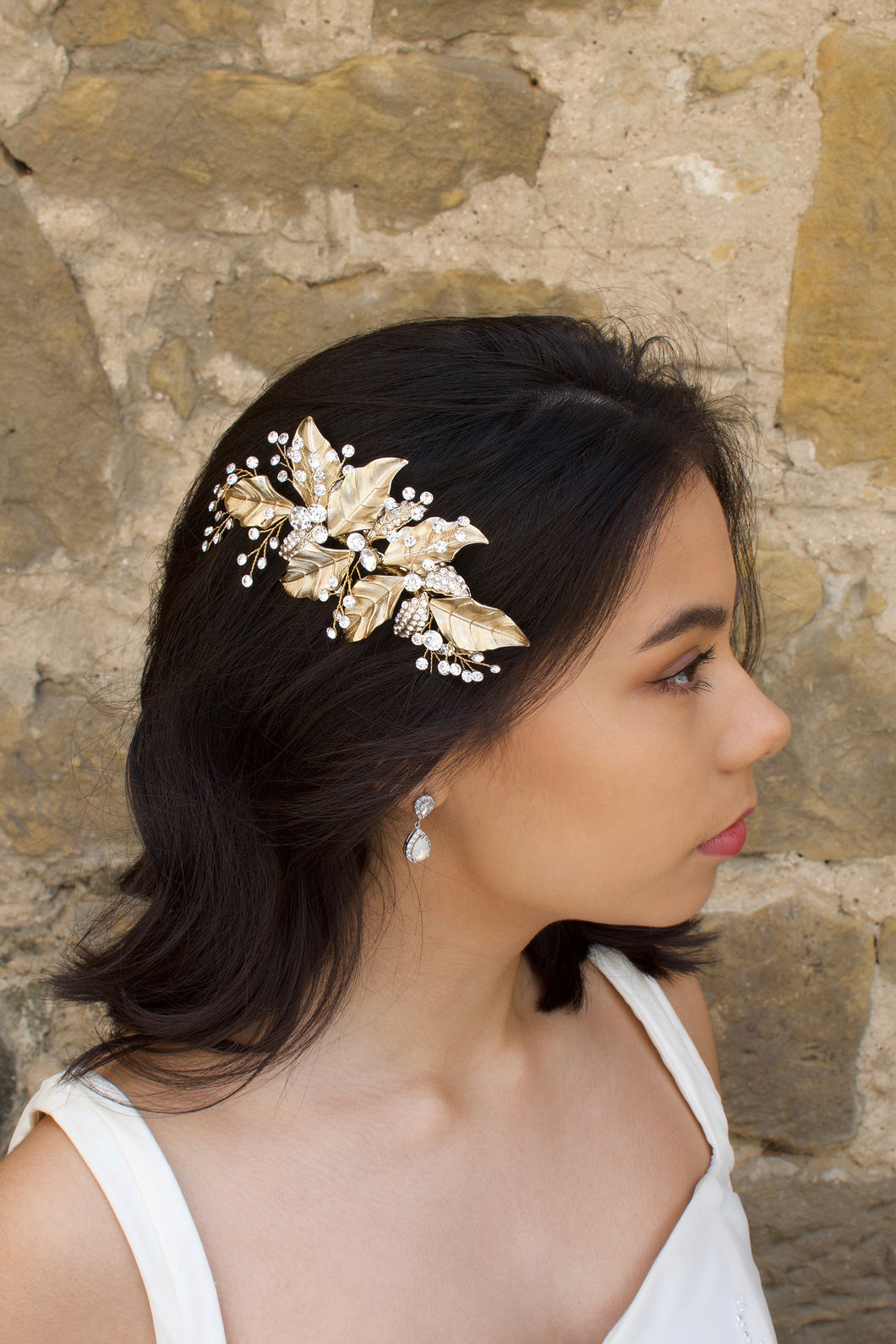 Gold leaf side comb worn by a dark hair bride standing beside a stone wall.