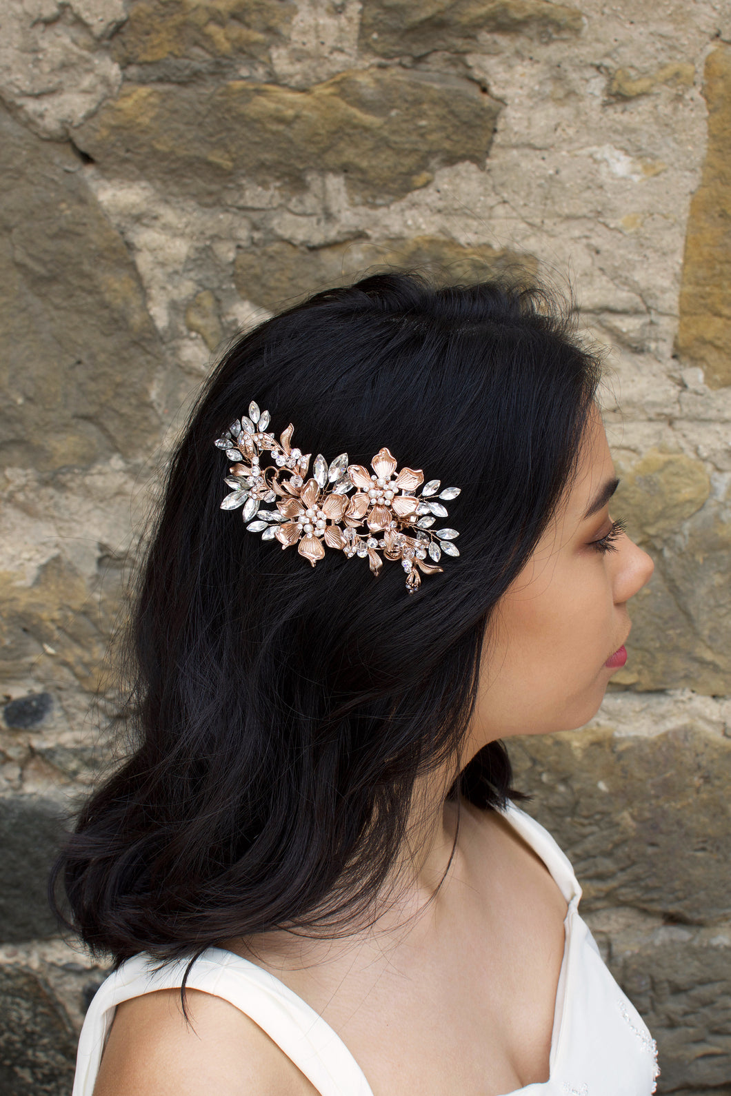 A dark haired model wears a Rose Gold flower comb on the side of her head. A stone wall is the background