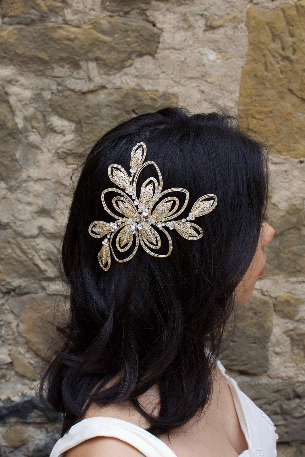 A dark haired bride wears a soft matt gold bridal side comb with a stone wall background