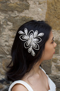 A dark haired bride wears a soft matt silver bridal side comb with a stone wall background