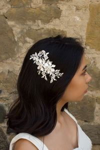 A dark haired model wears a Soft Silver flower comb on the side of her head. A stone wall is the background