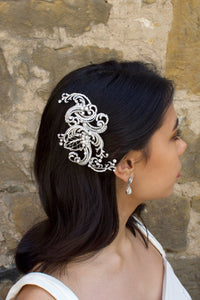 Model Bride wears a swirling side comb in her black hair with a stone wall background