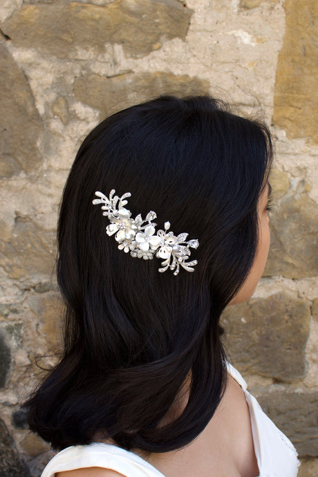 Model with dark hair wears a silver and flower side comb with a stone wall backdrop