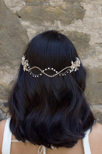 A Black haired model with her hair down wears a soft bridal vine at the back of her head. Stone wall background