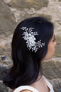 A model with lots of dark hair wears a pearl and crystal side comb on the side of her head in front of a stone wall