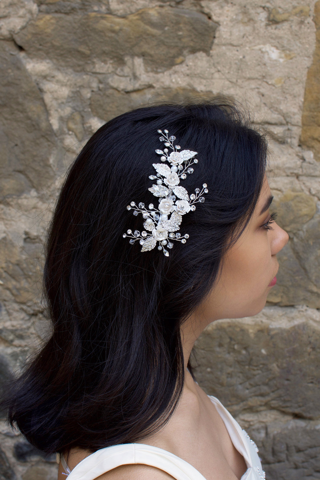 Pale Silver leaf and flower side clip worn by a dark hair bride with a stone wall background