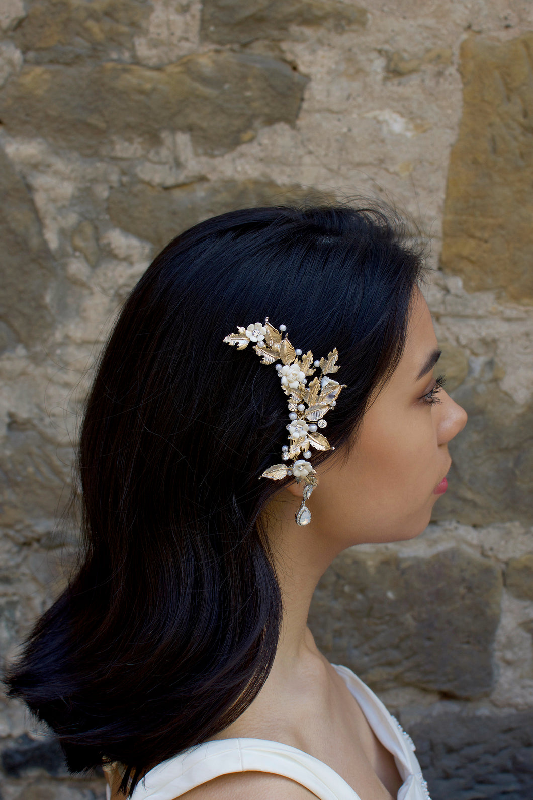 A Dark haired model  wears a rose gold side comb with a stone wall background
