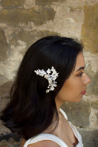 A Dark haired model with her hair down wears a rose gold side comb with a old stone wall background