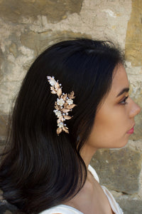 A Dark haired model with her hair down wears a rose gold side comb with a stone wall background