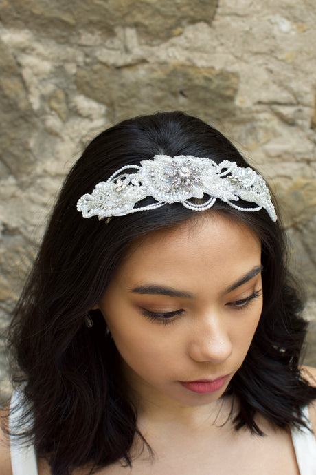 Dark Haired Bride wearing a seed pearl headpiece at the front on her black hair with a stone wall behind