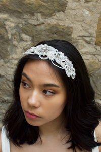 Bride with black hair wearing a seed pearl bridal comb at the front of her head with a stone wall background