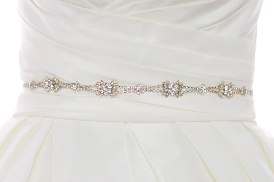 The waist of a bridal dress shown with a narrow Rose Gold belt worn around it with a white background