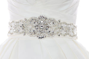 A wide bridal belt with crystals and beads worn on the waist of an ivory bridal gown with a white background