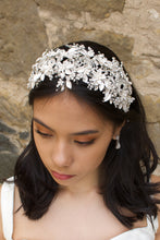 Load image into Gallery viewer, Black hair model wears a white leaves bridal headband that is wide with a stone wall behind her
